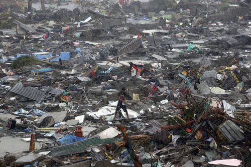 A man stands atop debris as residents salvage belongings from the ruins of their houses after Typhoon Haiyan battered Tacloban city in central Philippines November 10, 2013. One of the most powerful storms ever recorded has killed at least 10,000 people in the central Philippines province of Leyte, a senior police official said on Sunday, with coastal towns and the regional capital devastated by huge waves. Typhoon Haiyan destroyed about 70 to 80 percent of the area in its path as it tore through the province, said chief superintendent Elmer Soria, a regional police director. It not only brought wind gusts of around 275 kph (170 mph), it also caused a storm surge and whipped up waves of 5 to 6 metres (yards). REUTERS/Erik De Castro (PHILIPPINES - Tags: DISASTER ENVIRONMENT TPX IMAGES OF THE DAY) - RTX157B8