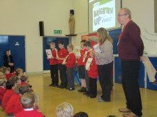 Two volunteers speaking to school assembly