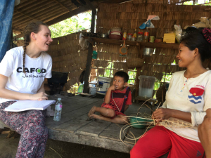 Lizzie talks to Samorn about life in the community as she weaves traditional fish traps.
